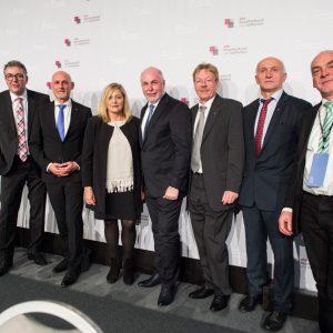 Menschengruppe vor weißer Wand