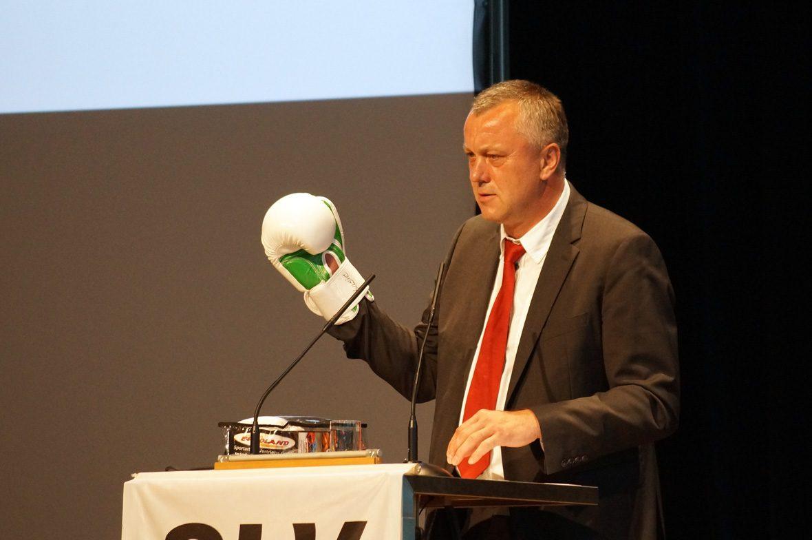 Redner mit Boxhandschuh am Pult